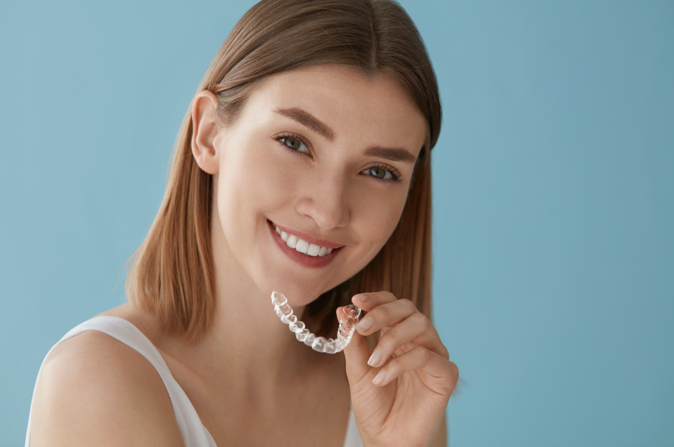 woman holding clear braces